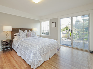 Bedroom with Wooden Floor and Sliding Glass Door leading to Balc